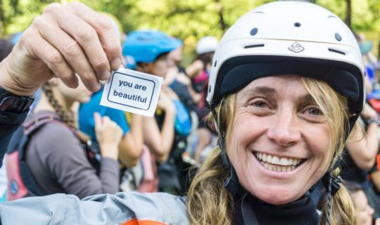 """Woman in paddling gear holding a """"you are beautiful"""" sticker"""