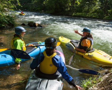 Three kayakers discussing route during the 5-Day Whitewater Kayaking/Canoeing Course