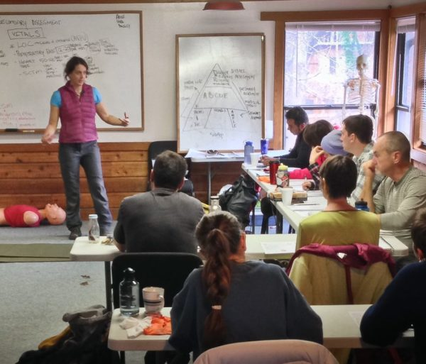 Woman by a whiteboard during the Advanced Wilderness First Aid (AWFA) Certification Course