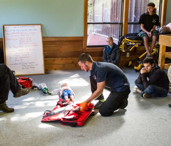 Man practicing CPR on a doll during the ASHI CPR and AED Certification Course