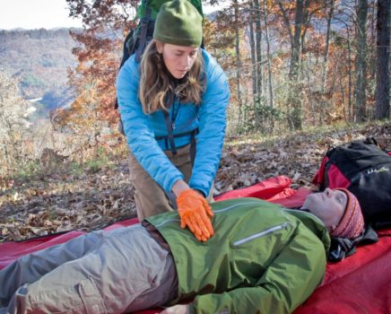 woman doing cpr on a man during the AWFA-WFR Bridge Course