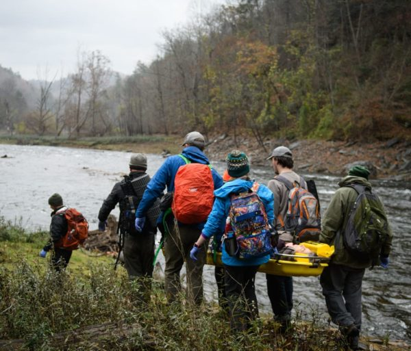 Group of people carrying a person in a stretcher by a river on the AWFA-WFR Bridge Course