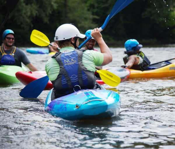 Guests learning to whitewater kayak on the Nantahala River- Intro to Whitewater Kayaking Trip