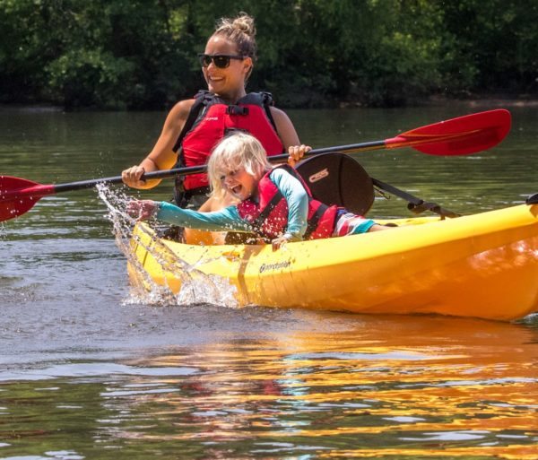 Child in a kayak splashing water on the Chattahoochee River Kayak Rentals - Roswell trip