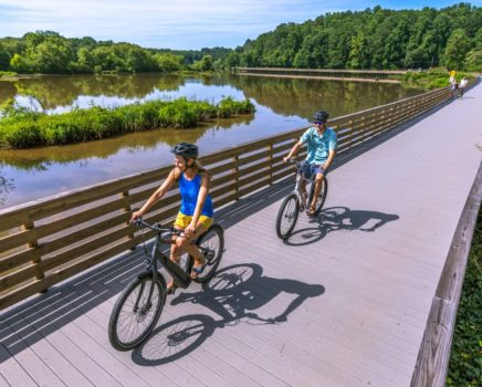 Two adults biking by water on the Chattahoochee River Bike Rentals – Roswell trip