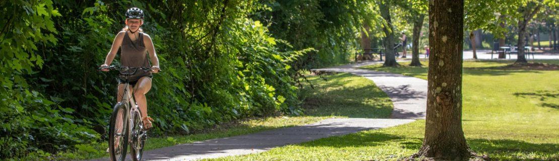 Young female adult biking on the Chattahoochee River Bike Rentals – Roswell trip