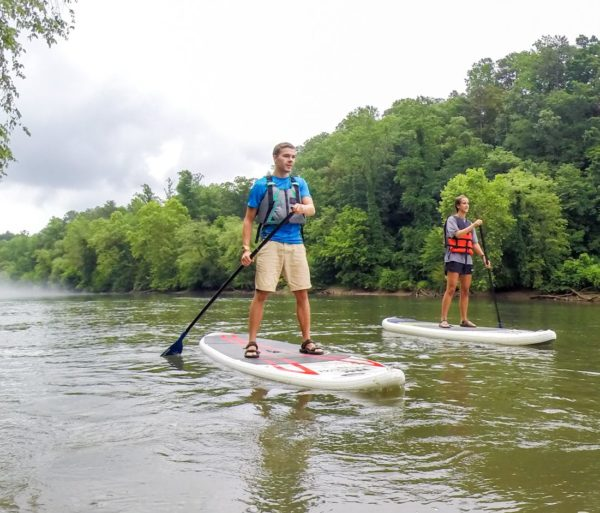 two young adults stand up paddle boarding