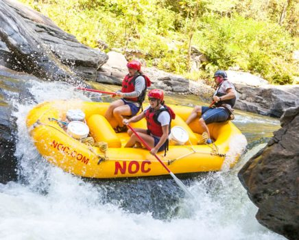 Yellow raft going over rapids on the Chattooga River Rafting: Section IV (with Lunch) trip