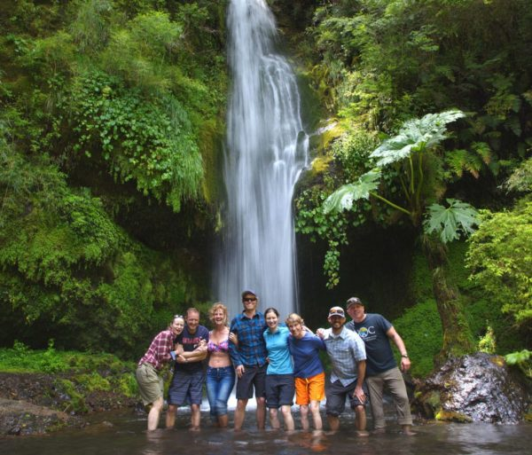 Guests standing under a waterfall on the Chile trip
