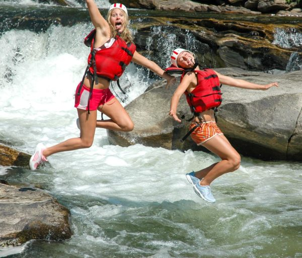 Two girls jumping into the chattooga river