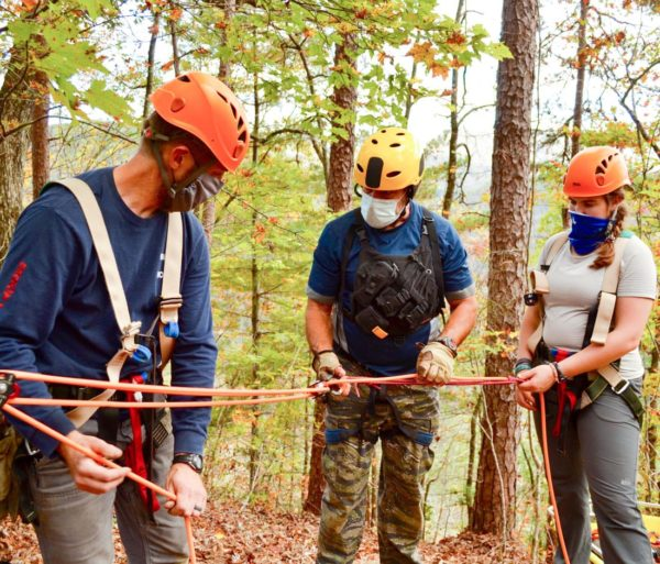 Three people in the woods doing LAST course training with ropes