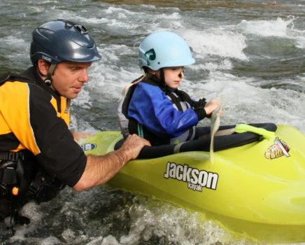 Instructor helping a child learn to kayak on the Private Canoe and Kayak Instruction course