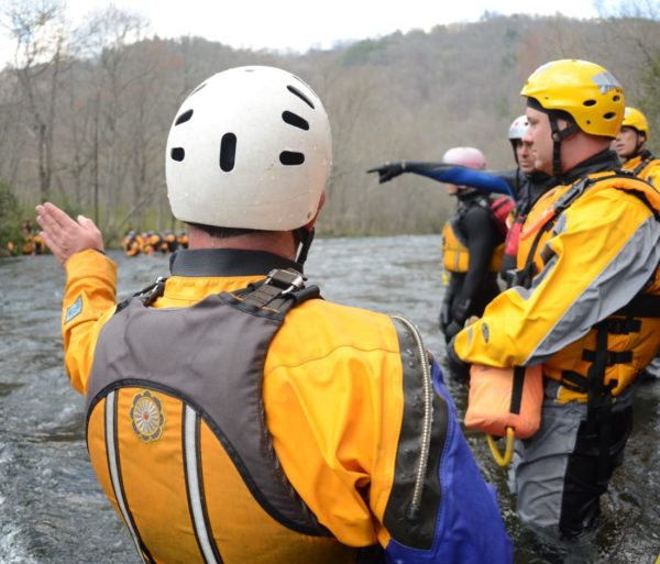 Pointing towards a specific spot on a river on the Rescue 3 Whitewater Rescue Technician (WRT) course