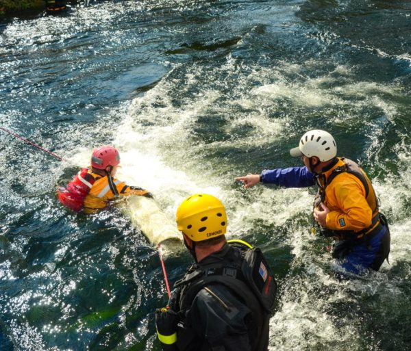 Tossing a throwbag to a swimmer during the Rescue 3 Whitewater Rescue Technician (WRT) course