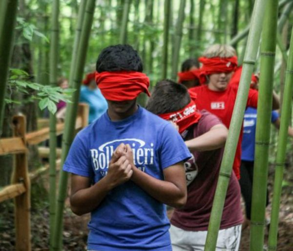 Teen blindfold walking during a team building activity outdoors