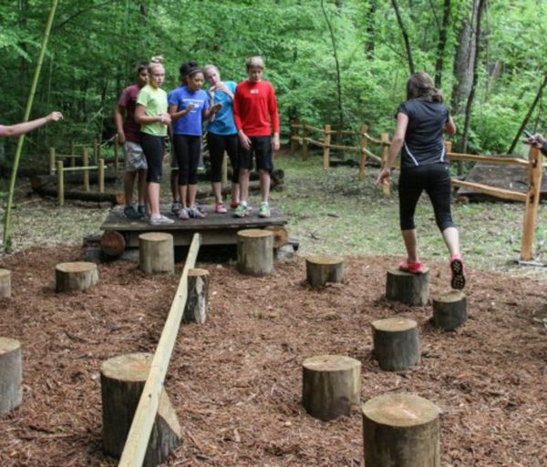 Teens crossing wooden stumps during a team building activity outdoors