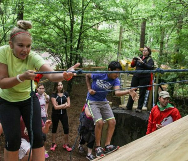 Teens using ropes during a team building activity outdoors