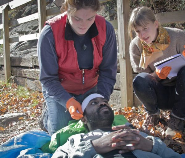 Woman lifting a man's head during the Wilderness First Aid (WFA) Certification Course