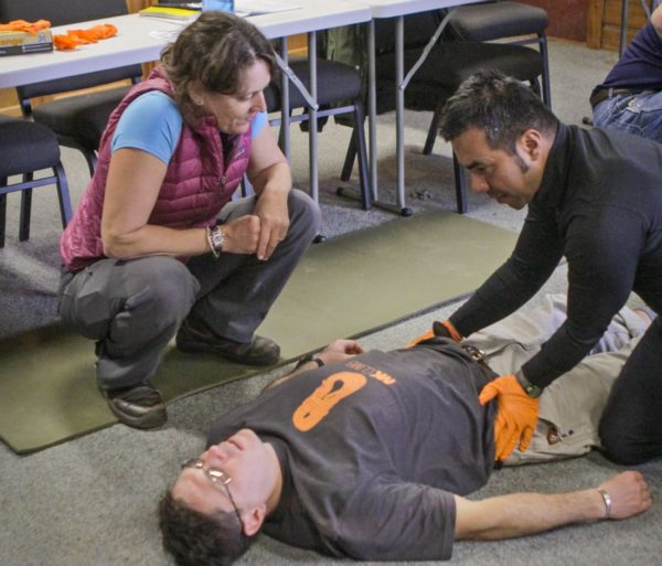 Student practicing medical techniques on man laying down during the Wilderness First Aid (WFA) Certification Course
