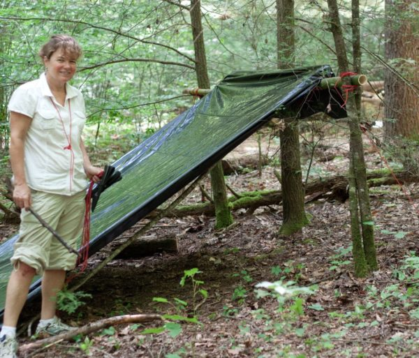Woman building a shelter out of tarp during the Wilderness Survival Instructor Training