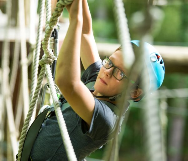 Youth climbing rope at the Zip Line Adventure Park