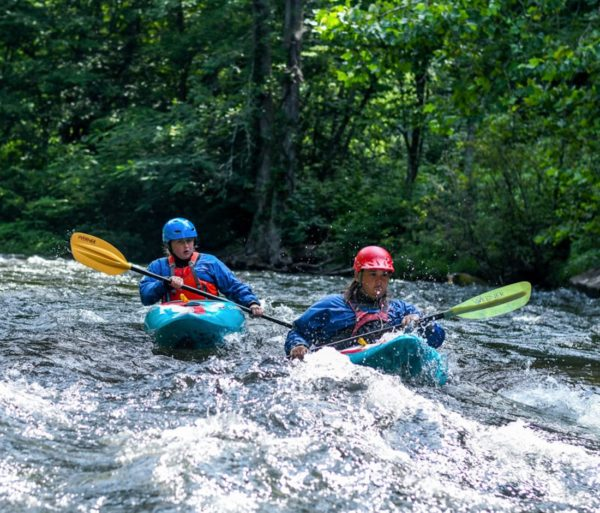 Two kayakers on a river during Advanced Teen Kayak Camp