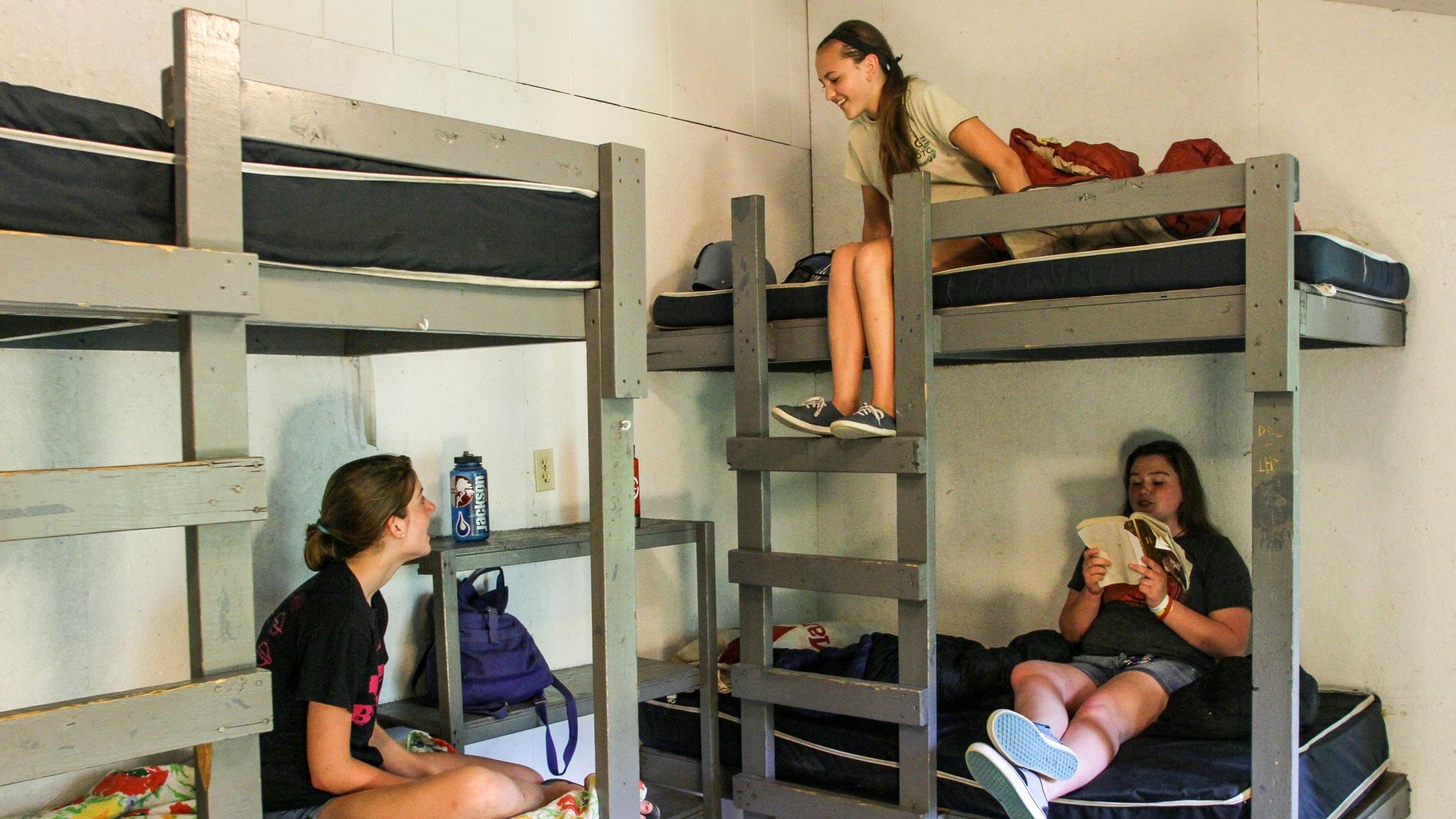 Three girls sitting in bunk beds at kayak camp
