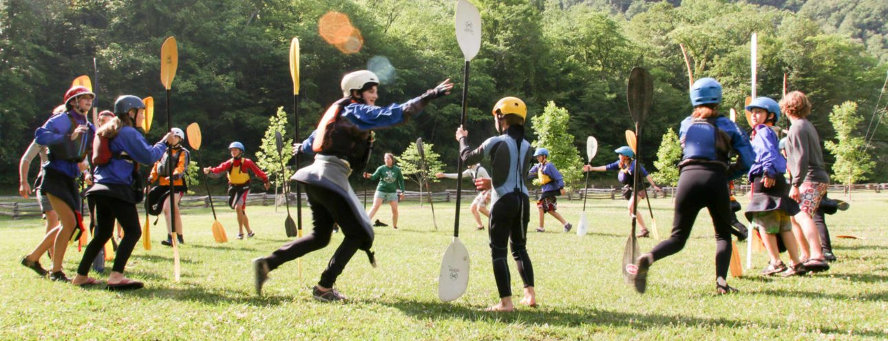 staff and campers playing lawn games at kayaking camp