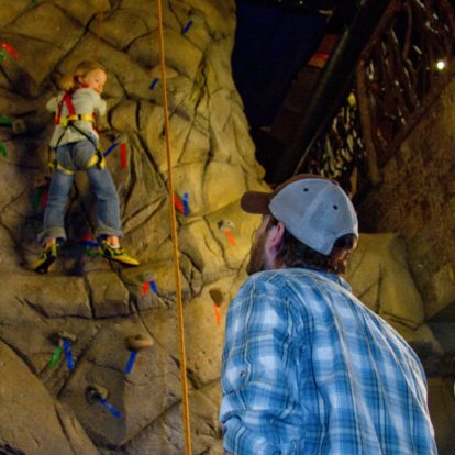 staff and youth on climbing wall in the NOC Gatlinburg store