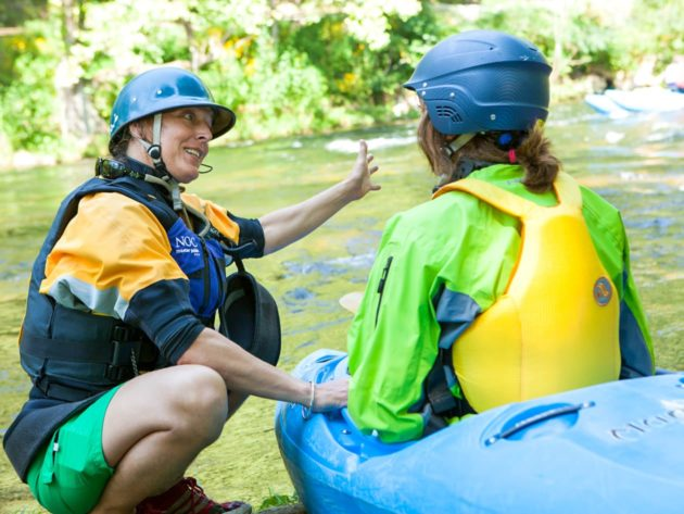 Student learning how to whitewater kayak from an instructor