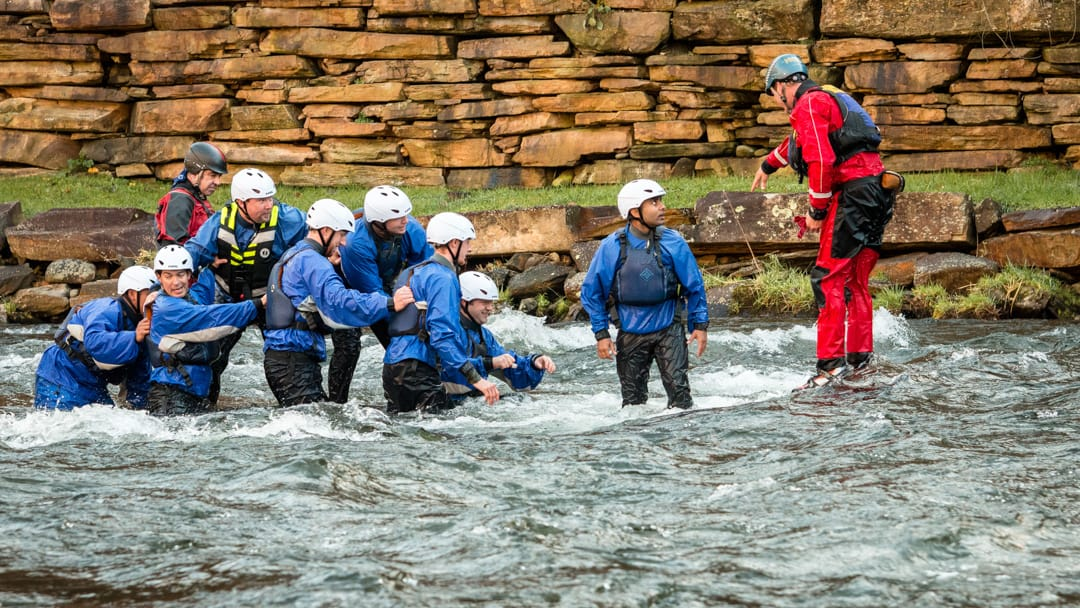 instructor and students in a river being rescued