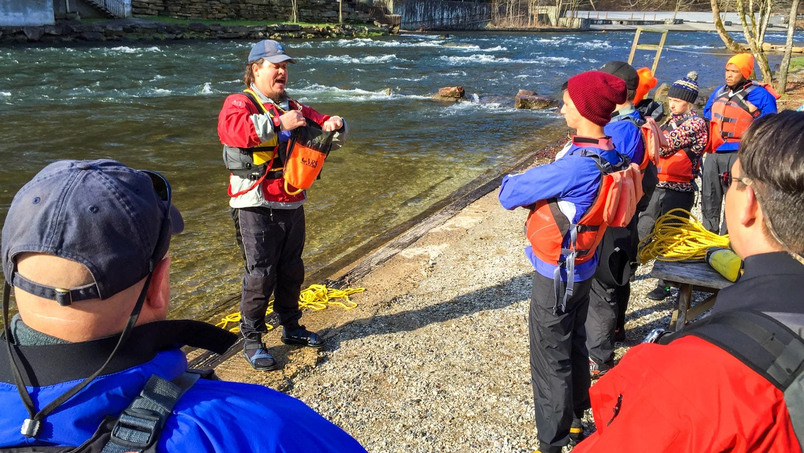 Instructor teaching students how to use a throw bag during raft guide school