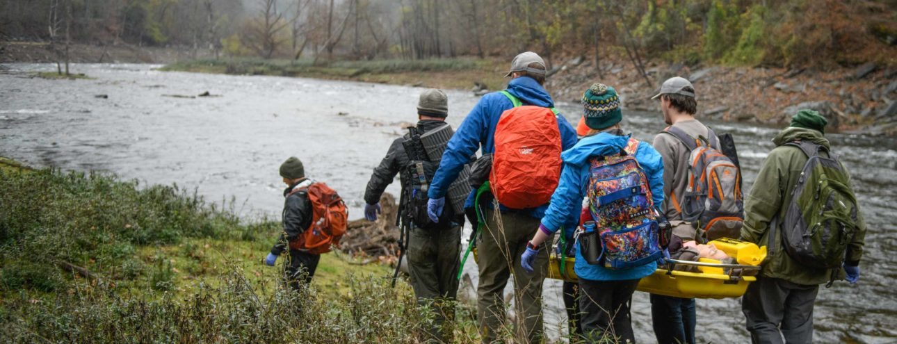 Adults walking towards a river while on the Wilderness Medicine (SOLO Southeast) course