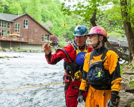 Instructors and students scouting a rapid during swiftwater rescue course