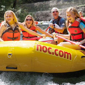 Group of guests rafting through whitewater