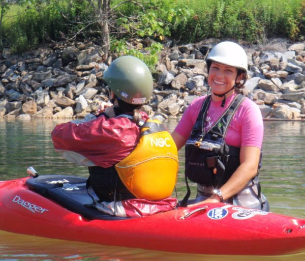 Instructor teaching student to roll on the Women's Weekend Kayak Retreat
