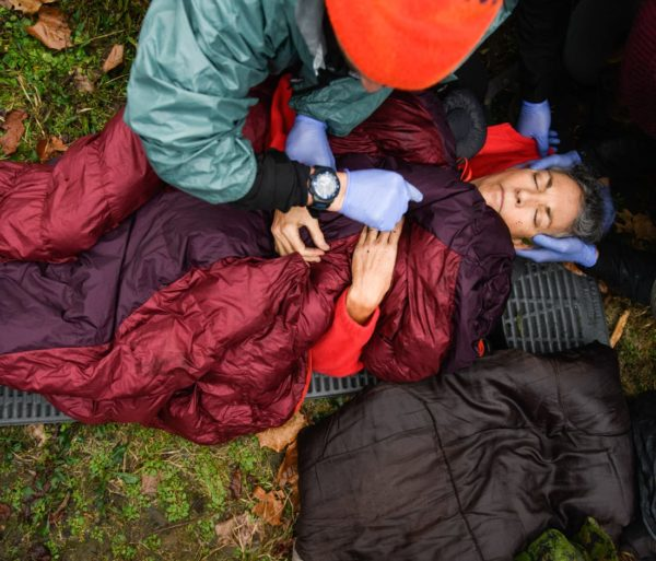 Person checking health of a man laying on the ground during the Wilderness First Responder (WFR) Certification and Recertification Courses