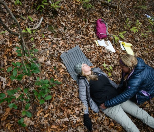 Person checking health of a woman laying on the ground during the Wilderness First Responder (WFR) Certification and Recertification Courses