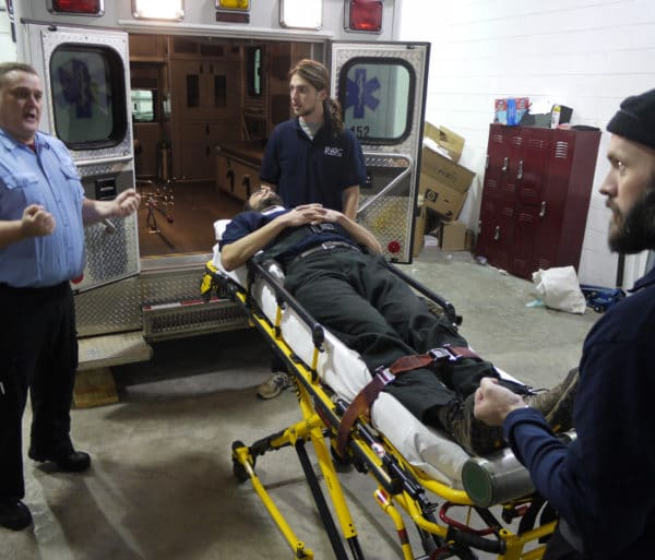 Carrying a person a stretcher into an ambulance