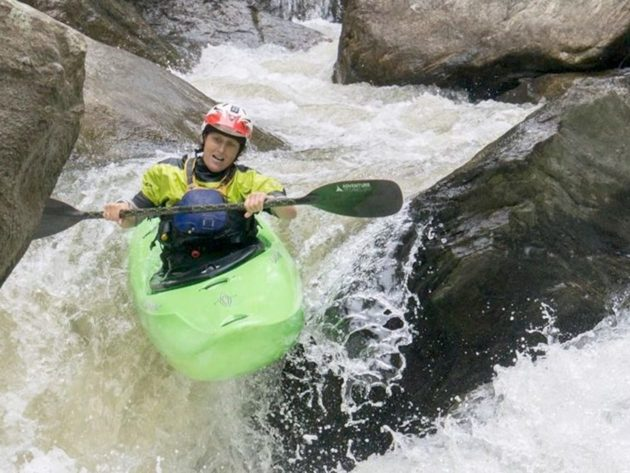 Anne kayaking through rapids on the NOC Women's Kayak Retreat