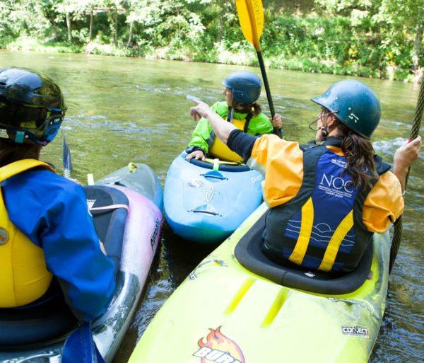 Three kayakers pointing