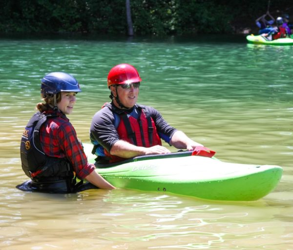 Instructor teaching student how to roll a kayak