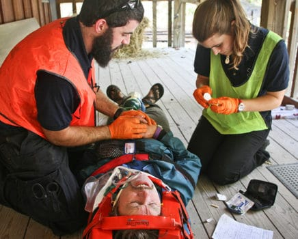Two people tending to a person in a stretcher