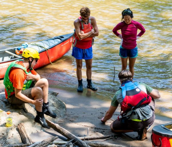 four paddlers standing by canoes
