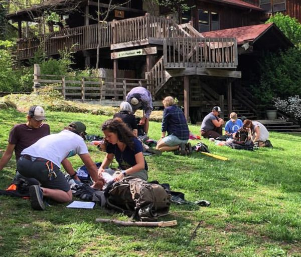 Students practicing wilderness healthcare too people in stretchers
