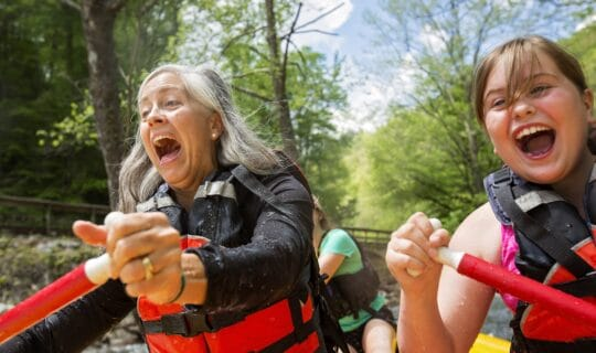 Woman and young girl whitewater rafting